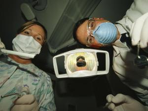 A Dentist and Dental Hygienist Prepare for an Examination by Joel Sartore