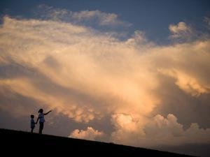 A Mother and Her Young Son Watch as a Thunderstorm Nears by Joel Sartore