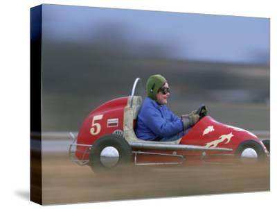 """A Young Boy Races a """"Midget Racer"""" Around a Track"""