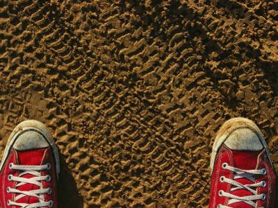 Red Sneakers on Soil Patterned with Tire Tracks