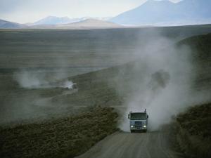 Trucks Traveling Through the Atacama Desert Stir up Clouds of Dust by Joel Sartore