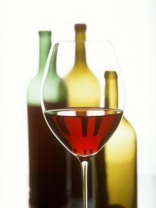 Glass of Red Wine in Front of Three Wine Bottles by Joerg Lehmann