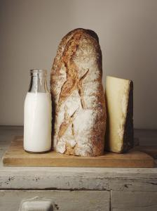Milk Bottle, Bread and Cheese on a Wooden Cupboard by Joerg Lehmann