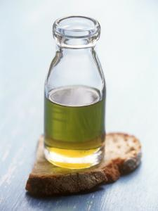 Olive Oil in Small Bottle and a Slice of Bread by Joerg Lehmann