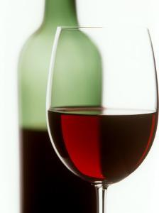 Red Wine Glass with Half-Full Wine Bottle in Background by Joerg Lehmann
