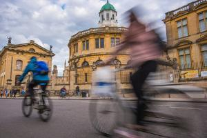 Cyclists Passing the Sheldonian Theatre, Oxford, Oxfordshire, England, United Kingdom, Europe by John Alexander
