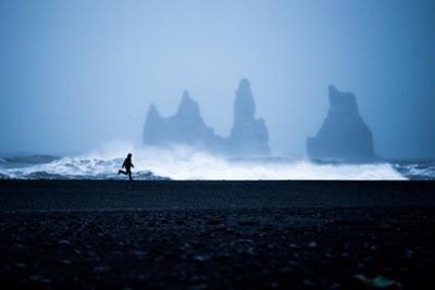 Tourist running on Black Sand Beach, Iceland, Polar Regions