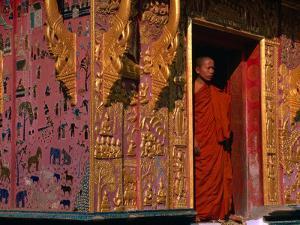 Buddhist Monk Standing in Doorway of Wat Xieng Thong, Luang Prabang, Laos by John Banagan