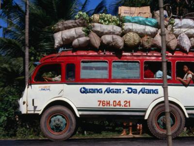 Bus Carrying Load and Passengers, Vietnam by John Borthwick