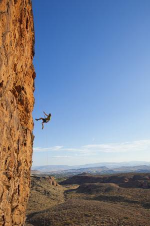 A Male Rock Climber Rappelling in Snow Canyon State Park by John Burcham