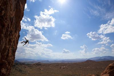 A Man Rappelling on the Red Rock Cliffs of Saint George, Utah by John Burcham