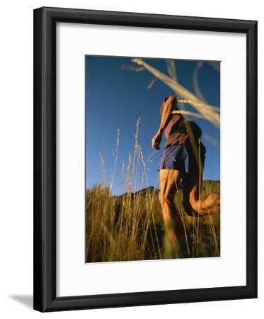 A Man Runs Through Tall Grass Near Mt. Elden