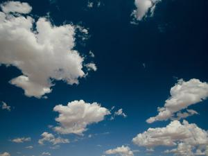 White, Fluffy Clouds Fill the Blue Sky Above Arizona by John Burcham