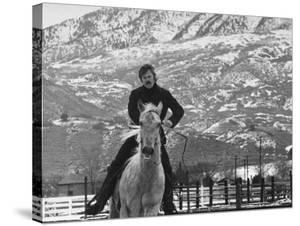 Actor Robert Redford Exercising One of His Eight Saddle Horses on His Remote Mountain Ranch by John Dominis