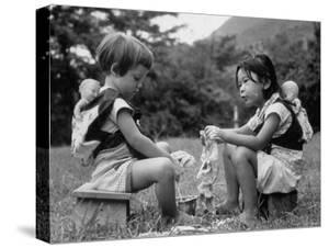 American Child Playing with Chinese Friend, Washing Doll Clothes by John Dominis