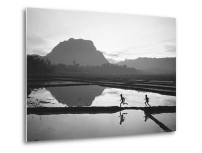 Boys Running Through Flooded Rice Paddy