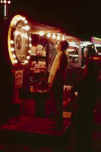 Fairgoer Stands on a 'Guess Your Weight' Carnival Game at the Iowa State Fair, 1955 by John Dominis