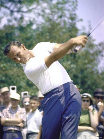Golfer Arnold Palmer Swinging Club as Spectators Look on at Event