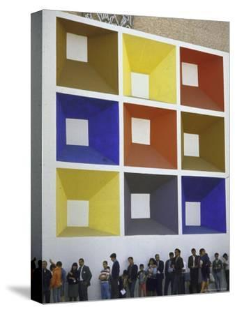 Line of People under Building Facade Painted with Brightly Colored Geometric Pattern