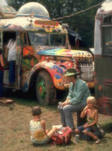 Man Seated with Two Young Boys in Front of a Wildly Painted School Bus, Woodstock Music Art Fest by John Dominis