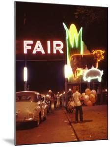 Man Selling Balloons at Entrance of Iowa State Fair by John Dominis