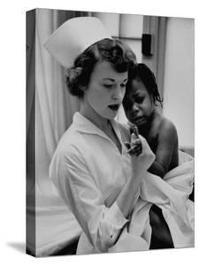 Nurse Holding African American Girl in Her Arms, Examining Her Finger by John Dominis