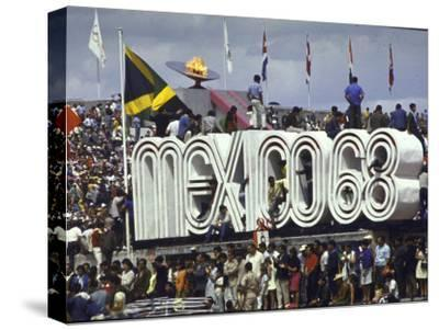 People Climbing and Sitting on a Mexico '68 Sign at the Summer Olympics