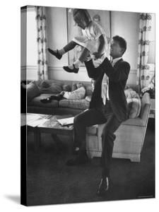 Robert F. Kennedy Playfully Tossing His Daughter Mary Kerry Kennedy Into the Air by John Dominis