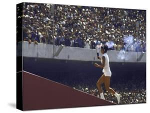 The Torch Being Carried Up the Steps in the Olympic Stadium at the Summer Olympics by John Dominis