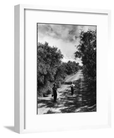 Two Children Walking Down a Dirt Road Going Fishing on a Summer Day