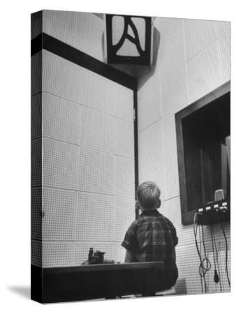 Young Boy Starring at the Loudspeaker Trying to Hear During a Medical Deafness Test