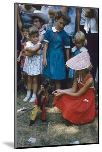 Young Girl in a Bonnet and a Red Dress Feeding an Organ Grinder's Monkey, Iowa State Fair, 1955 by John Dominis