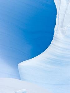 Blue Cave in Iceberg Sculpted by Waves by John Eastcott & Yva Momatiuk