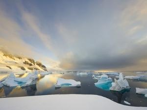 Evening Light on Mountains and Icebergs on Antarctic Peninsula by John Eastcott & Yva Momatiuk