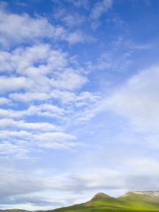 Green Hills Under Cumulus Clouds in Canada by John Eastcott & Yva Momatiuk