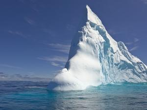 Pointy Blue Iceberg Sculpted by Waves by John Eastcott & Yva Momatiuk