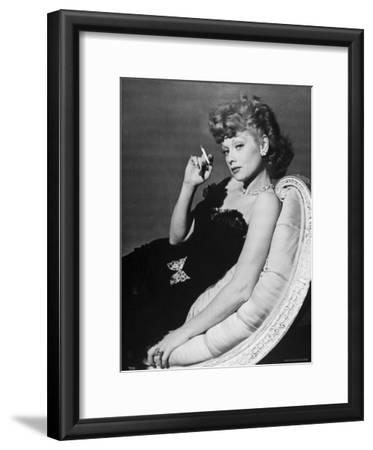 Dancer/Actress Lucille Ball in Strapless Black Lace Evening Dress, Holding Lit Cigarette on Couch