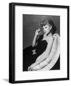 Dancer/Actress Lucille Ball in Strapless Black Lace Evening Dress, Holding Lit Cigarette on Couch by John Florea