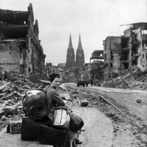 Homeless Refugee German Woman Sitting with All Her Worldly Possessions on Side of a Muddy Street by John Florea