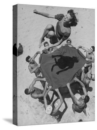 Teenaged Boys Using Blanket to Toss Their Friend, Norma Baker, Into the Air on the Beach
