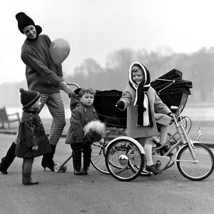 Jenny Boyd in Light Pants and Boots with Children, 1960s by John French
