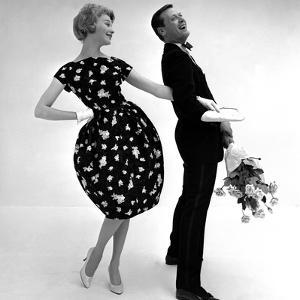 Model Wearing a Puff Ball Skirt and Escort with Roses, 1958 by John French