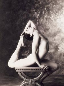 Ballerina Stretching Over Table by John Glembin