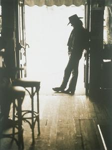 Cowboy Leaning in Doorway by John Halpern