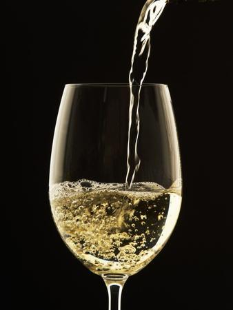 White Wine Pouring from Bottle into Glass