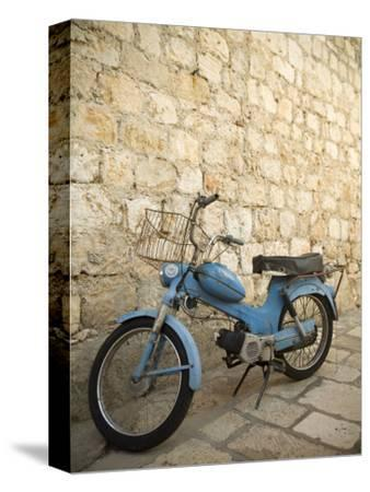 Blue scooter bike by old stone wall, Hvar Town, Hvar Island, Dalmatia, Croatia