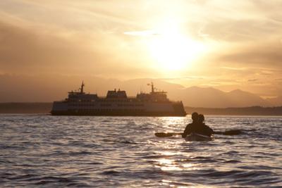 USA, Washington State, Seattle. Two-person sea kayak in Elliott Bay at sunset. by John & Lisa Merrill