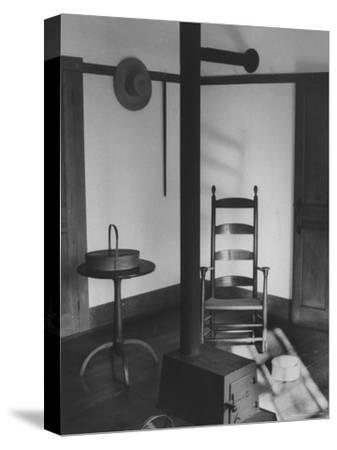 Iron Woodstove with a Ladder Backed Wooden Armchair in a Restored Shaker Parlor