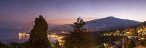 Panoramic view of Mount Etna and Giardini Naxos at dusk from Taormina, Sicily, Italy, Mediterranean by John Miller