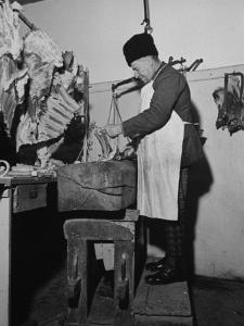 A Butcher Working in the Hungarian Meat Shop by John Phillips